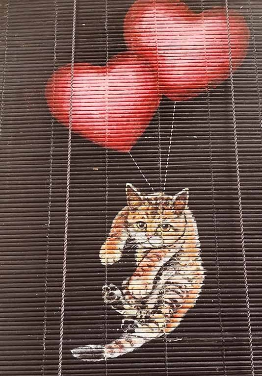 cat with flying heart balloons